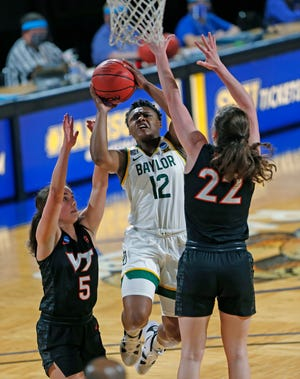 Baylor guard Moon Ursin (12) drives between Virginia Tech guard Georgia Amoore (5) and Virginia Tech guard Cayla King (22) during the first half of a college basketball game in the second round of the women's NCAA tournament at the Greehey Arena in San Antonio, Tuesday, March 23, 2021. (AP Photo/Ronald Cortes)