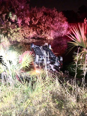 A police official said three Port St. Lucie police officers helped a woman out of a car that left the road and overturned in a retention pond off SW Galiano Road and SW Cadima Street on March 24, 2021.