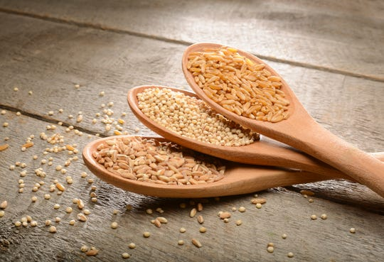 Ancient food grains in wooden spoons