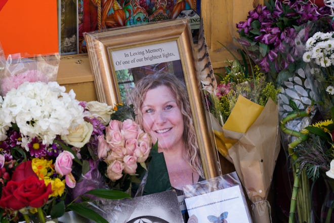A tribute is displayed outside the store owned by one of 10 victims in the mass shooting at a King Soopers grocery store, Wednesday, March 24, 2021, in Boulder, Colo. A shrine filled with candles and flowers kept growing Wednesday outside Umba Love, the clothing and accessories shop that victim Tralona Bartkowiak ran with her sister on Boulder's popular Pearl Street Mall. Bartkowiak died in the supermarket shooting attack on Monday. (AP Photo/David Zalubowski)