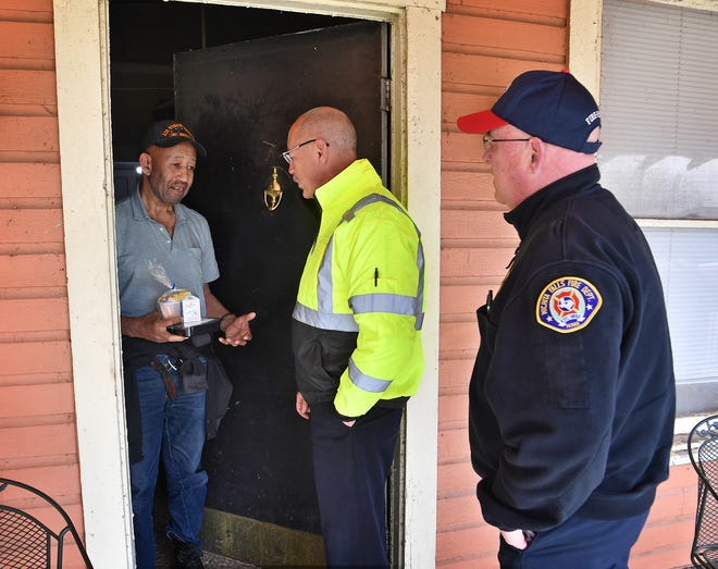 David Harriston talks with Wichita Falls Fire Chief Ken Prillaman and Deputy Chief Donald Huges after they delivered his Meals on Wheels during Community Champions Day Wednesday.