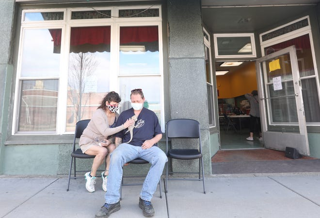 Sherri Francis and Tom Arbuckle wait out the post-vaccine recovery period after getting their COVID-19 vaccination at Christ's Table on Wednesday. With them is their pet horned lizard, Trigger.
