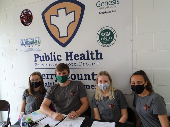 New Lexington High School juniors Emma Abrams (left), Hunter Kellogg, Maylynn Finley and Sydney Hambel work the vaccine clinic at the school's Workforce Development Center. The sign behind them signifies all the community partners working together at the clinics.