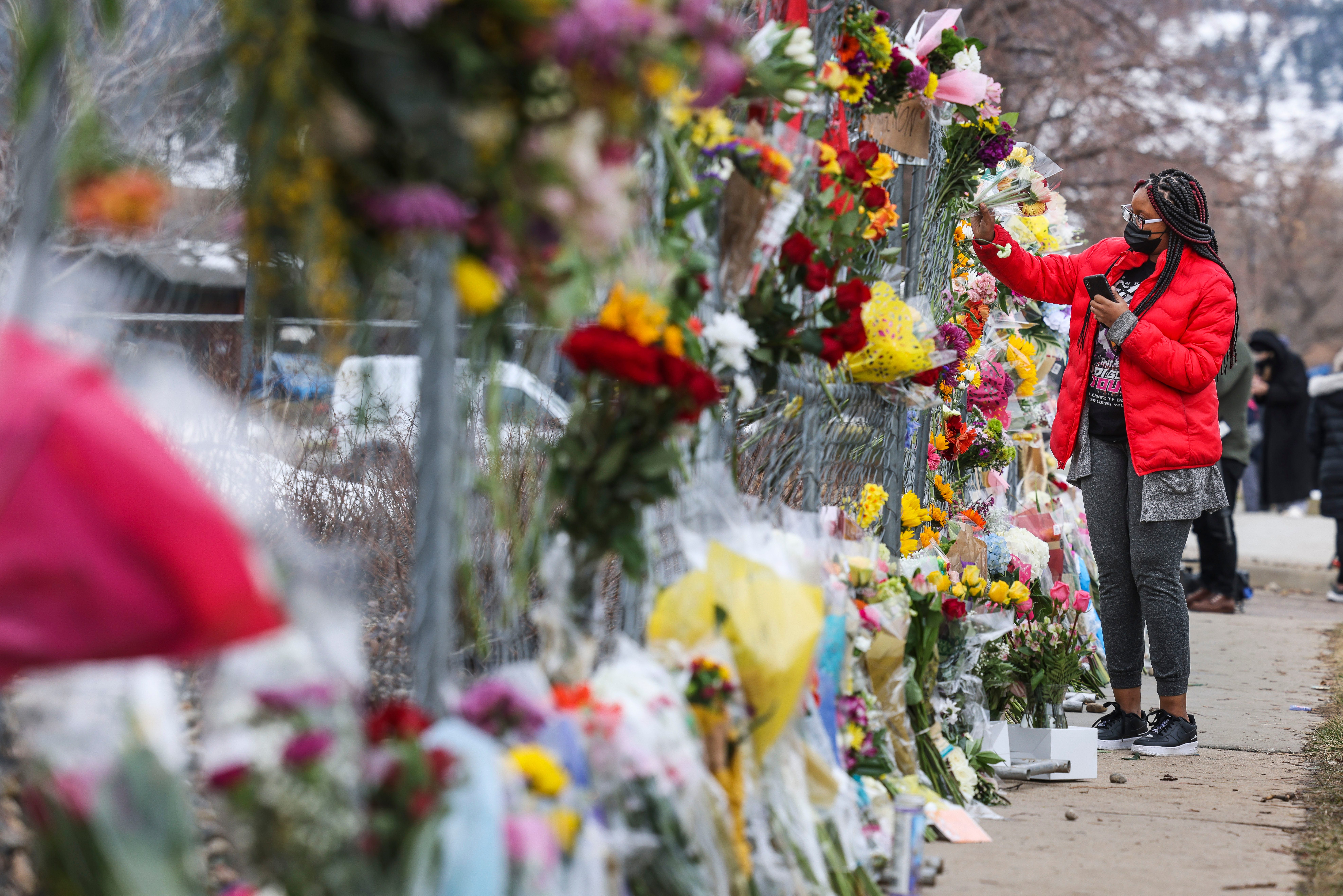 A woman places flowers at a memorial for the victims of the Colorado shooting.