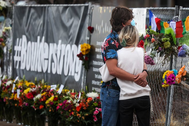 People hug at a makeshift memorial outside a King Soopers grocery store in Boulder, Colorado, on March 23, 2021.