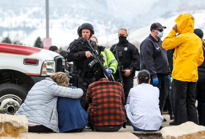 A woman comforts a pharmacy technician after a mass shooting at a grocery store in Boulder, Colorado, on March 22. One suspect is in custody, charged with killing 10 people, including a local police officer.