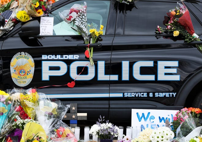 Flowers drape a police vehicle outside the Boulder Police Department after a shooting rampage at a Boulder supermarket on March 22 left 10 people dead, including officer Eric Talley, 51, a father of seven who responded to the 911 call.