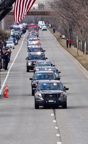 A procession of emergency vehicles on Wednesday escort the body of fallen Boulder police officer, Eric Talley, who was one of 10 people killed in a shooting at King Soopers grocery store in Boulder, Colorado.