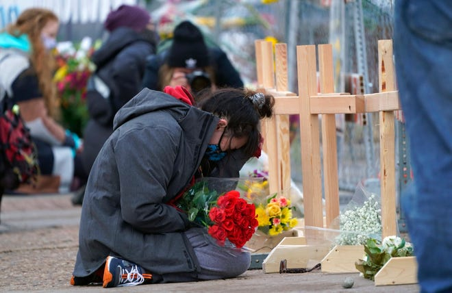 Star Samkus, who works at the King Soopers grocery store and knew three of the victims of a mass shooting at the store a day earlier, cries while kneeling in front of crosses placed in honor of the victims, March 23, 2021, in Boulder, Colo.