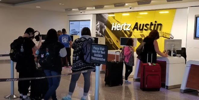 Travelers line up to pick up rental cars at Austin-Bergstrom International Airport on Thursday. Those who didn't make reservations in advance are finding they can't get a vehicle.