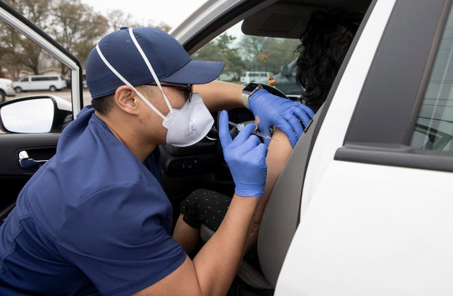 Pharmacist Jan Poquiz administers a COVID-19 vaccine at a drive-through vaccine clinic at Woodlawn Baptist Church in South Austin on March 10.