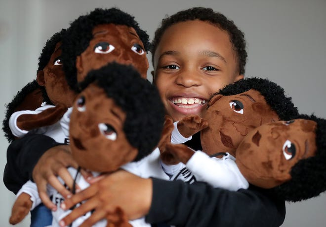 Demetrius Davis, 8, grins as he peeks over an armload of My Friend dolls that his business, Our Brown Boy Joy, sells with the help of his mother, Luciana Gilmore, in Twinsburg.
