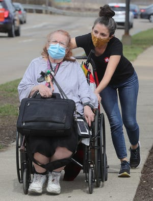 Katie Carver Reed of the Akron-Canton Regional Foodbank pushes Roberta Compton along Dart Avenue as she heads home from a food distribution event recently in Akron.