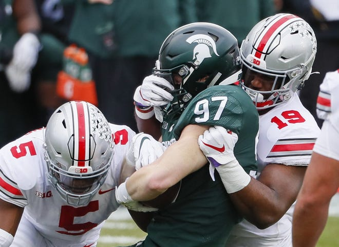 Ohio State linebacker Dallas Gant (19), here wrapping up Michigan State tight end Tyler Hunt in a December game, will miss all of spring football practice because of a foot injury.