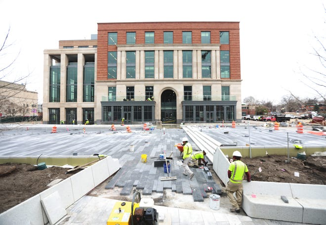 Workers install pavers on the area that used to be near the Flying Tomato restaurant's outdoor patio as work progresses on the 15th Avenue redevelopment across North High Street from Ohio State University.