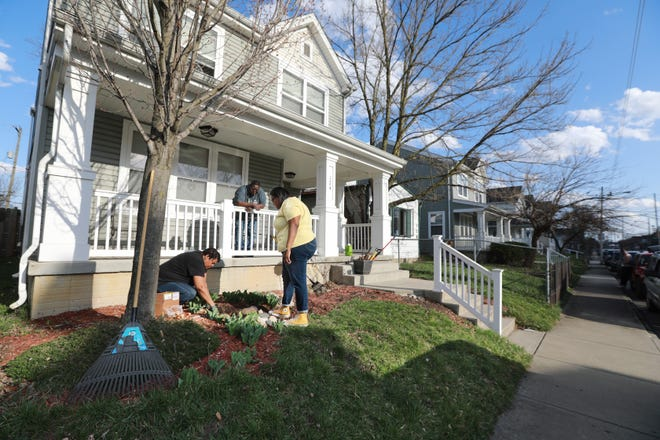 """Conchita Dillinger (left) plants flowers as her husband, Cornelius """"Butch"""" Dillinger, and their 22-year-old daughter, Jessica, watch in the front yard of their Franklinton home. The couple is worried they will soon be unable to afford to stay in their home because of gentrification and development around the neighborhood."""
