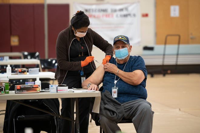 A Lake County school employee gets his COVID-19 vaccine recently at Tavares High School. [Cindy Peterson/Correspondent]