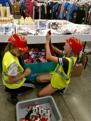 God Squad members Jessica Geiogue and Marina Albright go through bins looking for socks at the Clothing Warehouse in Medina in April 2019 to donate to homeless people.