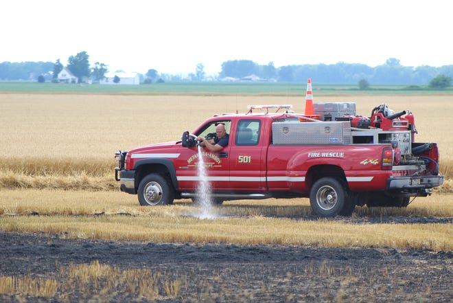 A firefighter from Metamora-Amboy Volunteer Fire Department in Ohio sprays down hot spots in a wheat field at the corner of Mulberry Road and Neuroth Highway on July 6, 2020. The field caught fire while farmers were harvesting wheat.