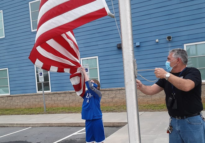 Davidson Charter Academy students, like third-grader Riley Myers, get to help facilities manager Jason Berube take down the flag at the end of the school day. Berube recently won the NC Educational Lottery School Hero award.
