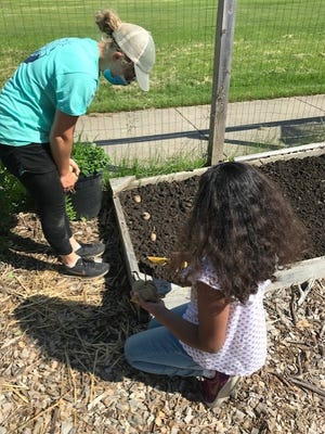 A student and teacher work together in an Erie School District garden.