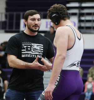 Burlington High School's head wrestling coach Matt Seabold, wearing a t-shirt with the school's new logo, greets BHS wrestler Daniel Remele as he heads back the team's bench, following his 220lb match against Mount Pleasant's Trevor Wellington, Thursday Jan. 30, 2020 at BHS. Seabold is leaving BHS to take a position as strength and conditioning coach at Bettendorf.