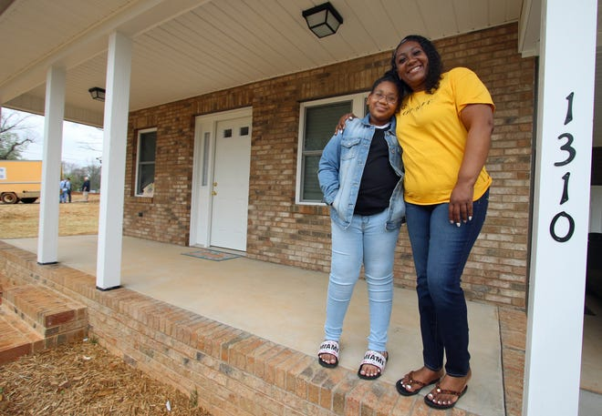 10-year-old Azaria Addison and her mother, Tamica Addison, pose outside their new home as members of Habitat for Humanity help build homes in the Vermont Village Community on Gidney Street in Shelby Thursday afternoon, March 25, 2021.