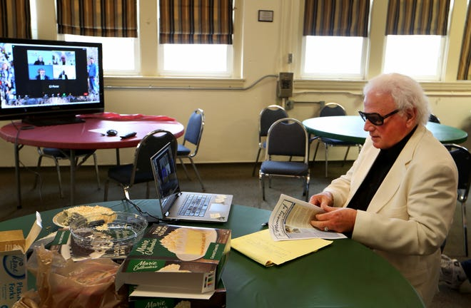 Kelvin O'Brien picks up a photograph of his brother Conroy O'Brien to show to the Kansas Prisoner Review Board during a March 25 online parole hearing. O'Brien came back to his hometown to address the board with other Abbyville community members in opposition to the parole of Jimmie Nelms, who murdered Conroy in 1978.