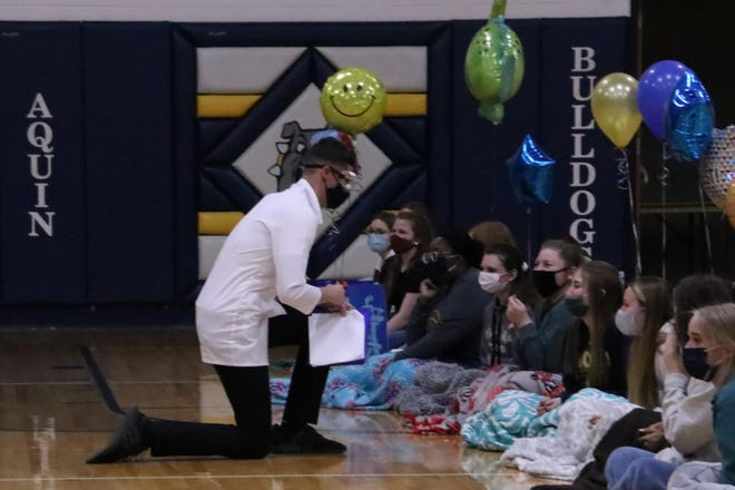 Junior Connor Senneff asks Senior Ashley Lamm to the prom after drawing her name at Aquin High School's annual Prom Draw.
