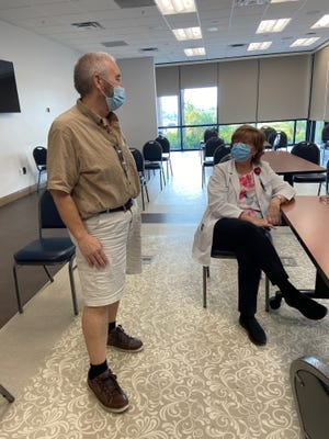 Chriss Scovil stands up to showcase his weight loss in a follow-up visit with Marianne Lehman, director of the bariatric surgery weight-loss program at  AdventHealth Heart of Florida.