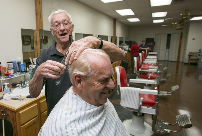 "Herbert ""Boots"" Hooker works on Stan Elliott's hair at his shop in Ocala's Six Gun Plaza on Nov. 26, 2014. The longtime barber — his first job cutting hair was in 1960 — died earlier this month of natural causes. [FILE]"
