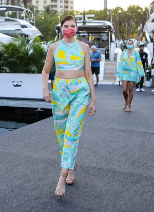 Bright patterns of greens and yellows grace a pants-and-crop-top ensemble as well as a long-sleeved A-line dress.