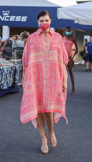 A model shows off a flowy caftan in melon colors.