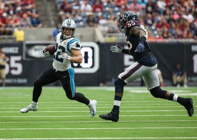 Carolina Panthers running back Christian McCaffrey runs with the ball as former Houston Texans inside linebacker Benardrick McKinney defends.