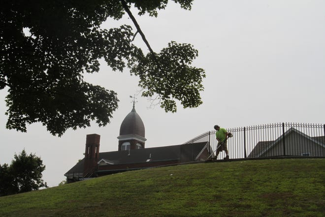 City Hall in Central Falls looms over the horizon as a grounds keeper clears leaves and twigs in Jenks Park July 13, 2012.