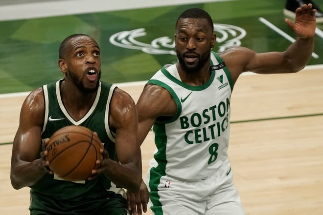 Milwaukee Bucks' Khris Middleton shoots past Boston Celtics' Kemba Walker during the first half of an NBA basketball game Wednesday, March 24, 2021, in Milwaukee. (AP Photo/Morry Gash)