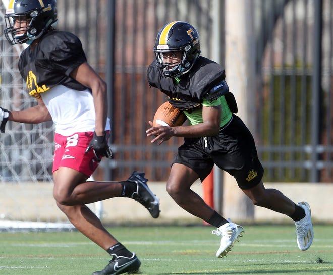 Ranado McKay follows a blocker as he runs back a punt return during Central High School football practice.