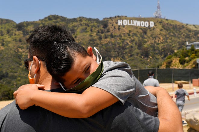 FILE - In this May 15, 2020, file photo, a father holds his son near the famed Hollywood sign during the coronavirus outbreak in Los Angeles. (AP Photo/Mark J. Terrill, File)