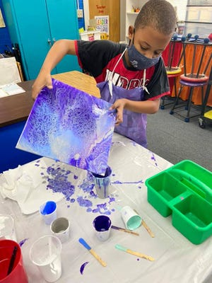 A student at Horace Mann finishes up an acrylic pour painting.
