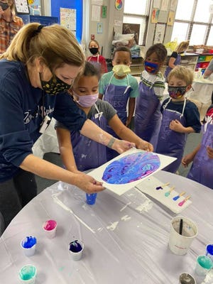 Phyllis Bolt helps during the acrylic pour class at Horace Mann.