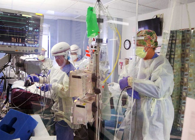 Cinthya Cruz, RN, and Nicole Hart, RN, reset monitoring equipment for a patient who is diagnosed with COVID-19 as nurses and medical staff work in unison to turn a patient over, a treatment method called proning. The noninvasive treatment is one of of the care strategies implemented to help patients.