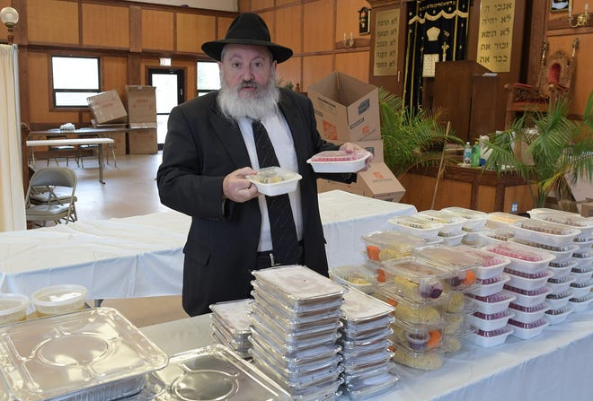 Rabbi Mendel Fogelman Wednesday describes items included in a complete seder dinner distributed to 250 families by his Central Mass. Chabad in Worcester. The event is usually held in person at the Newton Avenue site and last year after the pandemic struck it was marked by a large-scale distribution of matzo to Jewish families across the region.  Fogelman and his wife, Chani, decided this year to go big with a full-course boxed meal as a show of appreciation to God for their health.
