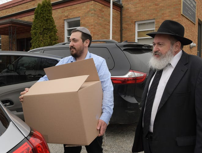 Rabbi Leivik Fogelman, left, and Rabbi Mendel Fogelman load a box containing the items for a complete seder dinner into a car outside the Central Mass Chabad in Worcester Wednesday. About 250 of the boxes were distributed for families to observe Passover this weekend.