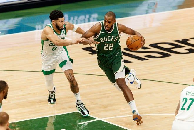 Bucks forward Khris Middleton drives for the basket past Celtics forward Jayson Tatum during the first quarter Wednesday night in Milwaukee.