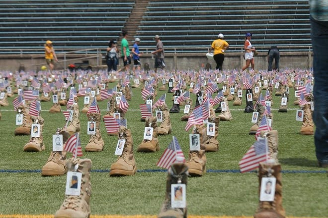 Volunteers place more than 7,500 boots at Hedrick Statidum at Fort Bragg in May 2019. Officials say they need more than 1,000 boots for this year's memorial display.