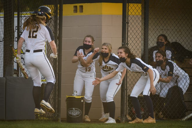 Cape Fear's Meaghan Himes jumps in the air and is cheered on by her teammates after hitting a home run against Gray's Creek on Wednesday, March 24, 2021, at Cape Fear High School.