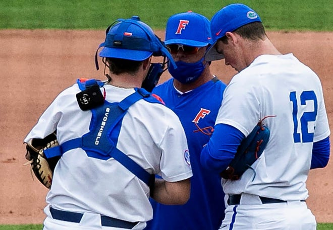 Florida coach Kevin O'Sullivan goes over the game plan last week with pitcher Hunter Barco, right, and catcher Mac Guscette.