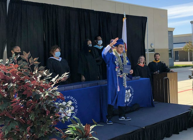 A Cobalt Institute of Math and Science graduate waves to his family during the school's 2020 graduation ceremony. CIMS was among just three schools in the county named a California Distinguished School this year.