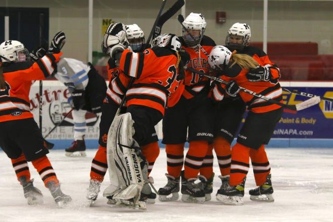 Teammates mob Middlebury goalie Abby Hodsden after she made 25 saves to help the Tigers beat South Burlington 2-1 in the Division II girls hockey championship on Wednesday, March 24, 2021 in Barre.