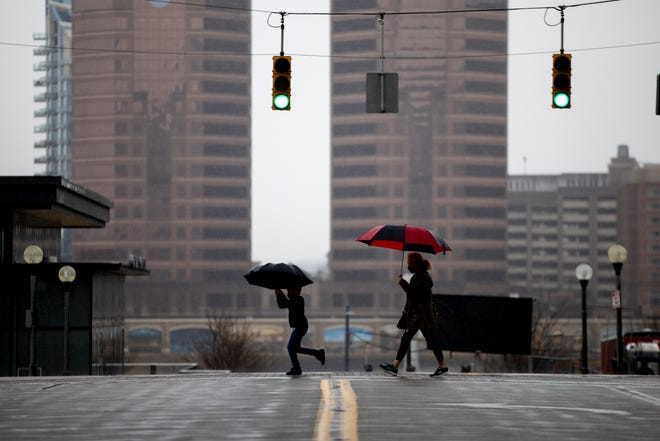 Pedestrians walk through the rain in Downtown Cincinnati on Thursday, March 25, 2021. The National Weather Service is expecting thunderstorms and wind gusts of 60 MPH in the Cincinnati region on Thursday night.
